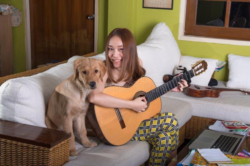 Bella ragazza asiatica che gioca felicemente chitarra con il cane fotografia stock libera da diritti