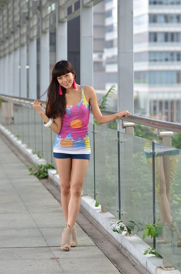 Bella ragazza asiatica che mostra vigore giovanile sul ponte pedonale fotografia stock libera da diritti