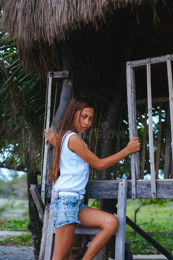 Bella ragazza asiatica che posa sulle scale della casa sull'albero sulla spiaggia fotografie stock libere da diritti