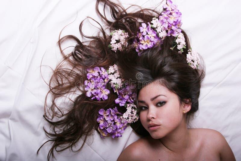 Bella ragazza asiatica con i fiori fotografia stock libera da diritti