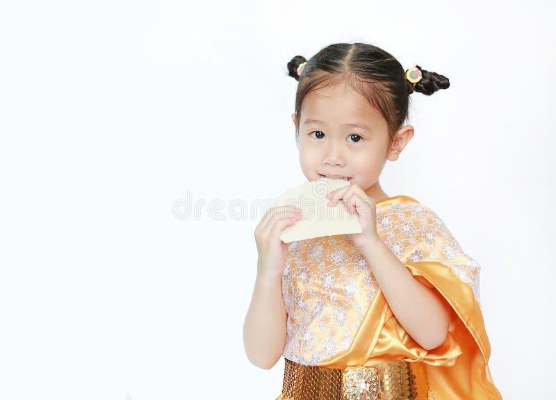 Bella ragazza asiatica del bambino in vestito tailandese tradizionale che mangia la caramella del dessert dello strato isolata su immagine stock