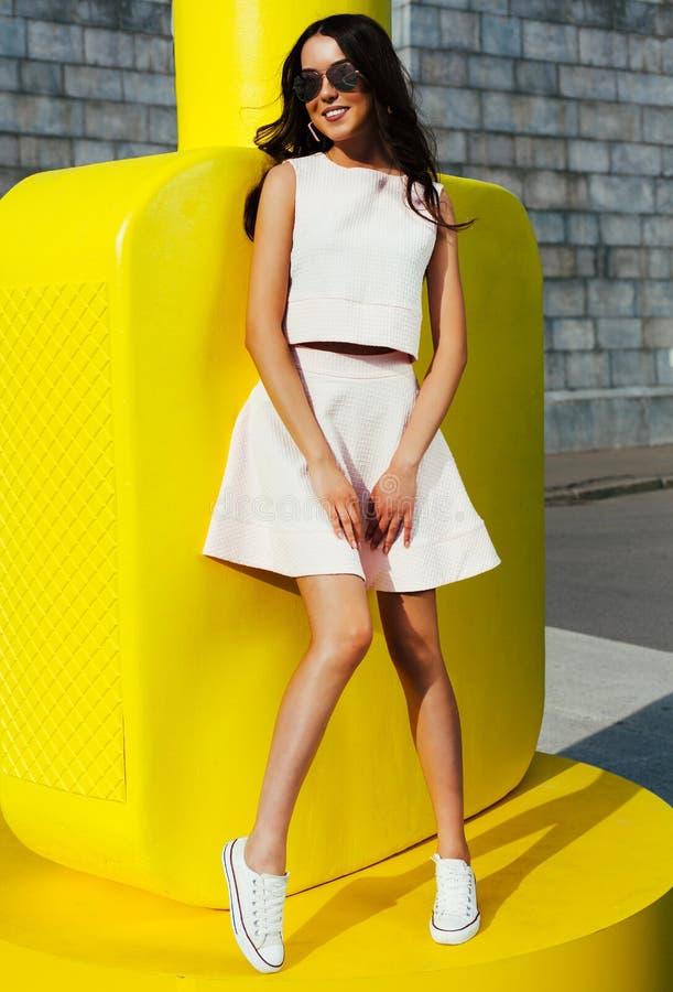 Bella ragazza asiatica in occhiali da sole ed attrezzatura luminosa di estate che posano contro lo sfondo di grande bottiglia gia fotografia stock