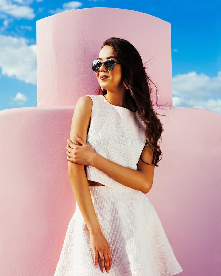 Bella ragazza asiatica in occhiali da sole ed attrezzatura luminosa di estate che posano contro lo sfondo di grande bottiglia ros immagini stock