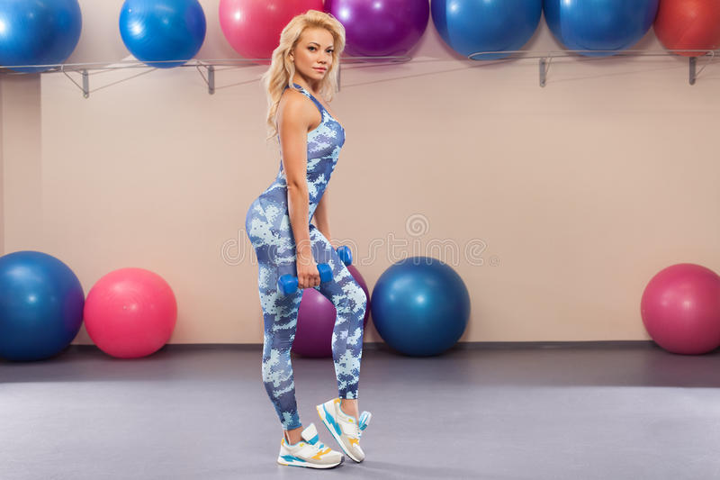 Bella ragazza atletica che fa esercizio nella stanza di forma fisica Donna di sport nell'allenamento degli abiti sportivi fotografia stock libera da diritti