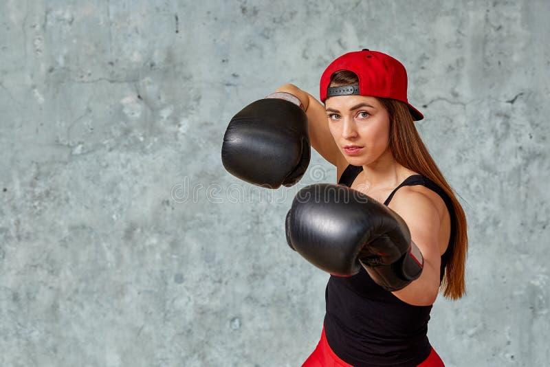 Bella ragazza atletica che posa in guantoni da pugile rosa su un fondo grigio Copi lo spazio, primo piano Sport di concetto, lott fotografie stock libere da diritti