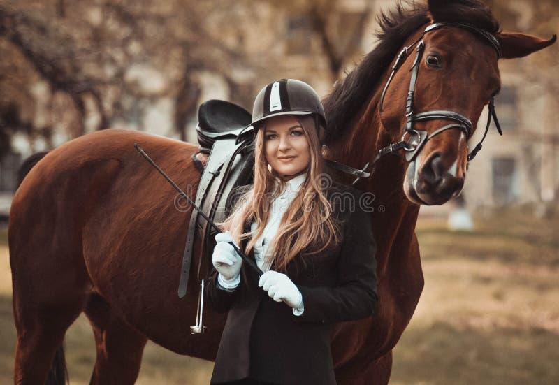 Bella, ragazza attraente con un cavallo Amazzone professionista, cavallerizza immagini stock