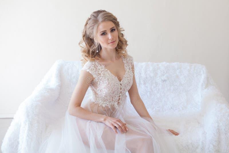 Bella ragazza in biancheria che si siede sulle nozze bianche dello strato fotografie stock libere da diritti