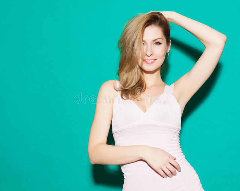 Bella ragazza bionda alla moda divertendosi e felicemente posando su un fondo verde nello studio Riscaldi tonificato fotografie stock
