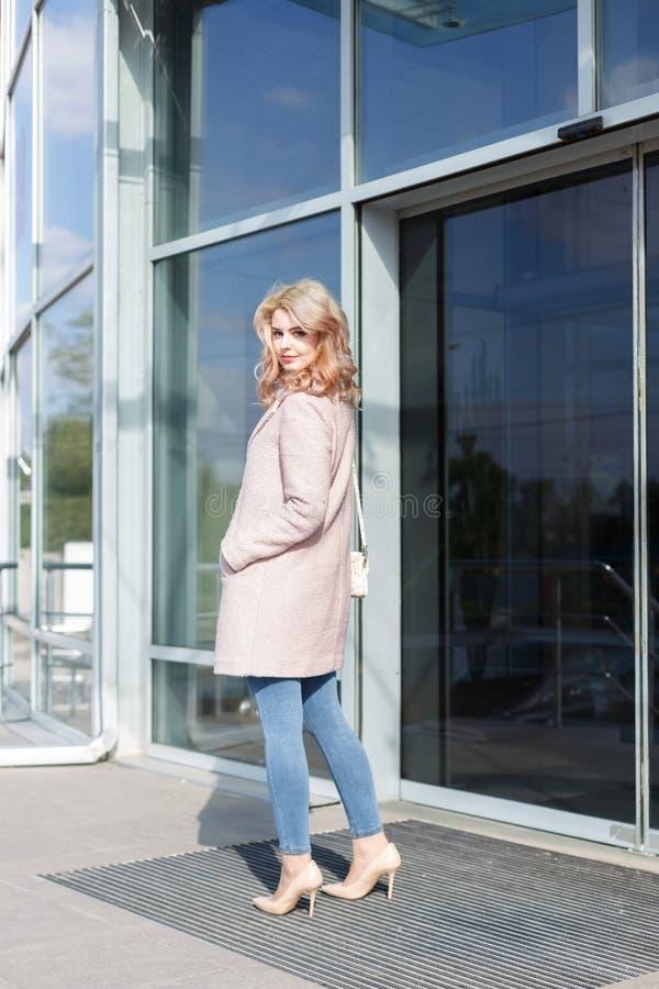 Bella ragazza bionda in bello cappotto beige, jeans e tacchi alti fotografia stock libera da diritti