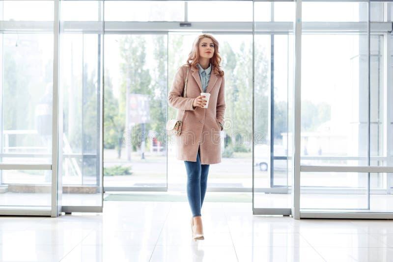 Bella ragazza bionda in bello cappotto beige, jeans e tacchi alti immagine stock libera da diritti