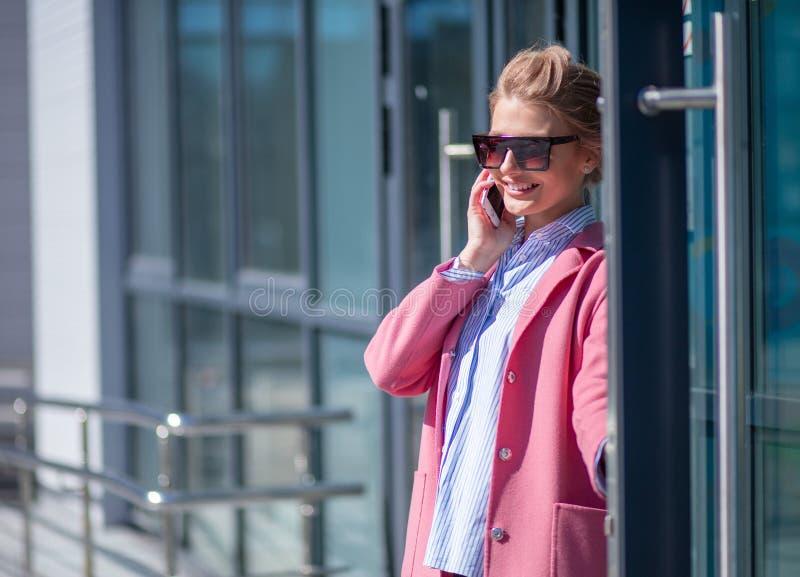 Bella ragazza bionda in cappotto di lusso dopo avere fatto spesa fotografia stock