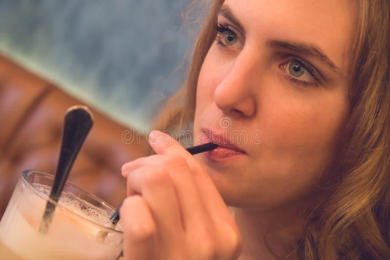 Bella ragazza bionda che beve il caffè del latte Fine in su fotografia stock libera da diritti