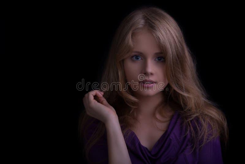 Bella ragazza bionda che guarda alla macchina fotografica, toni scuri fotografia stock