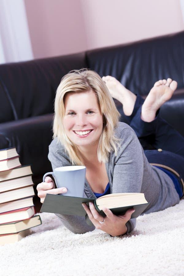 Bella ragazza bionda che legge felicemente. fotografie stock libere da diritti