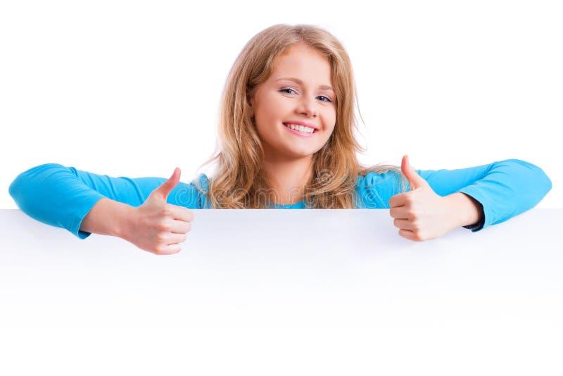 Bella ragazza bionda che mostra i pollici su dietro un boa bianco vuoto fotografie stock