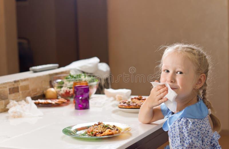 Bella ragazza bionda che pulisce la sua bocca su un tovagliolo immagini stock