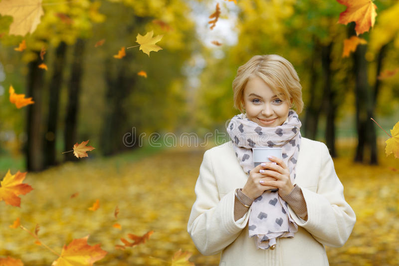 Bella ragazza bionda che tiene tazza di tè caldo in bello autunno immagine stock