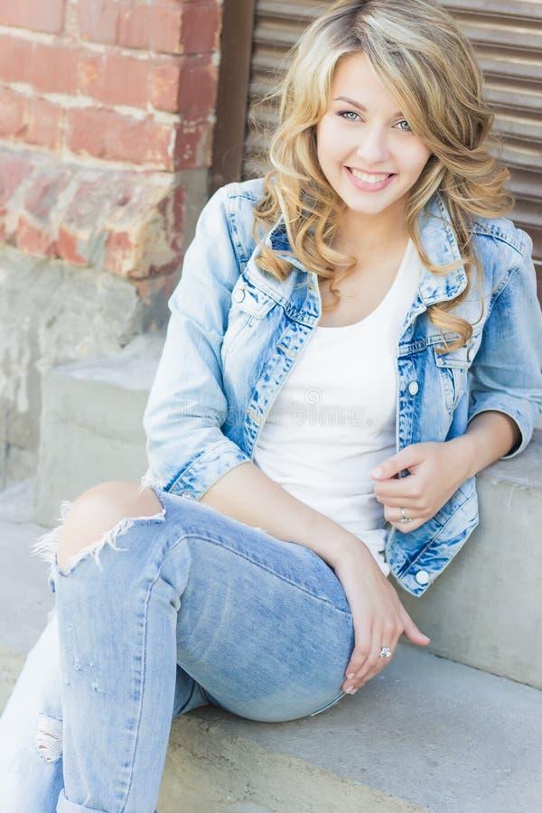 Bella ragazza bionda divertente con le grandi labbra con i jeans di uso, di sorriso e una camicia bianca affascinanti camminante  fotografia stock libera da diritti