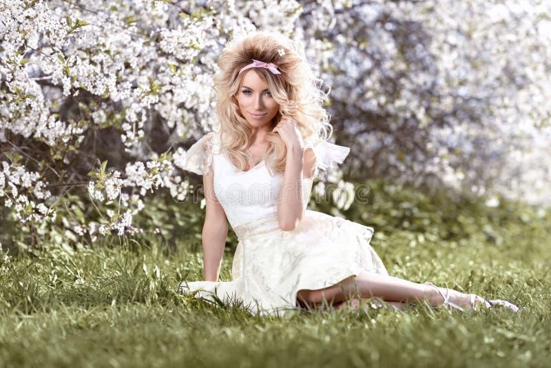 Bella ragazza bionda nei colori di fioritura dell'annata del giardino della ciliegia fotografia stock libera da diritti