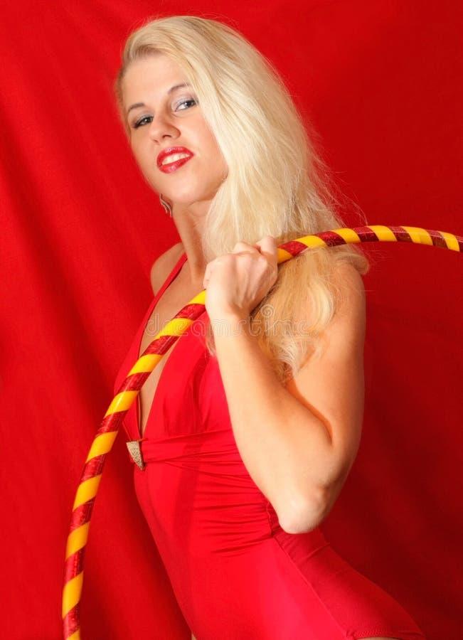 Bella ragazza bionda nel hula-hoop rosso della tenuta del vestito fotografie stock libere da diritti