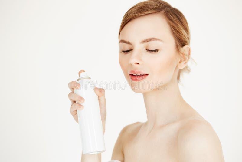 Bella ragazza bionda nuda con pelle perfetta fresca che sorride esaminando la bottiglia dello spruzzo di cosmetologia della tenut fotografie stock