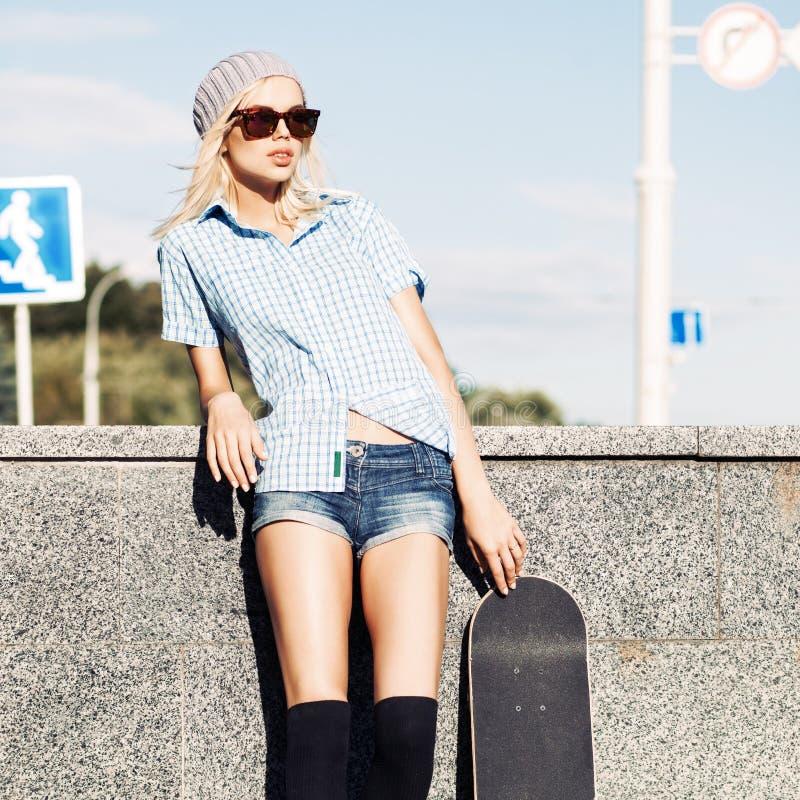 Bella ragazza bionda in pantaloncini corti con il pattino fotografie stock libere da diritti