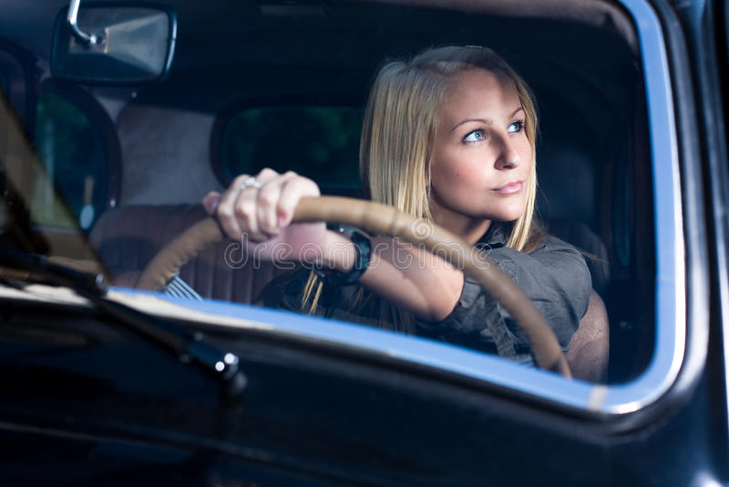 Bella ragazza bionda in un'automobile nera dell'annata. immagine stock