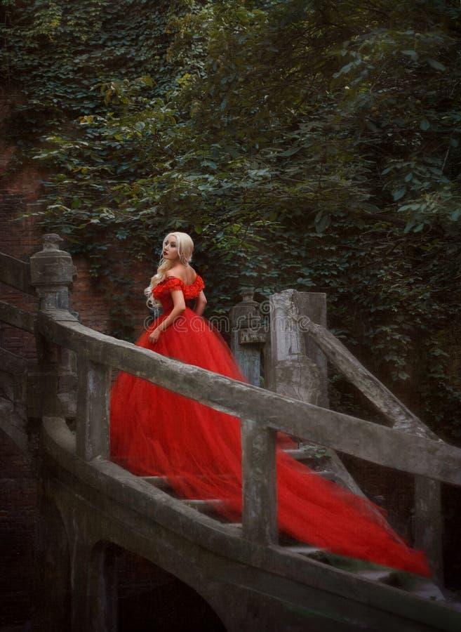 Bella ragazza bionda in un vestito rosso lussuoso fotografia stock