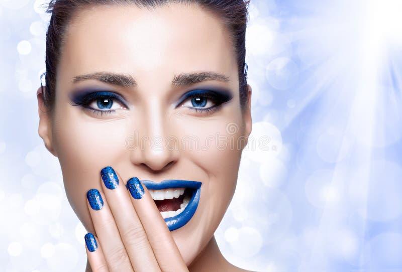 Bella ragazza in blu con la mano sul suo fronte Arte e Makeu del chiodo immagini stock