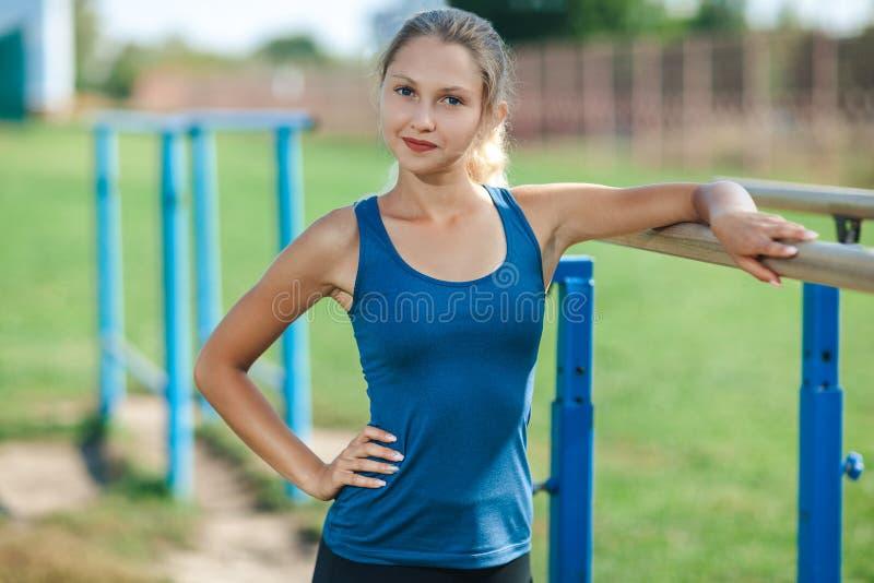 Bella ragazza in camicia blu e ghette sulle barre irregolari sul campo sportivo all'aperto di estate che esamina macchina fotogra immagine stock