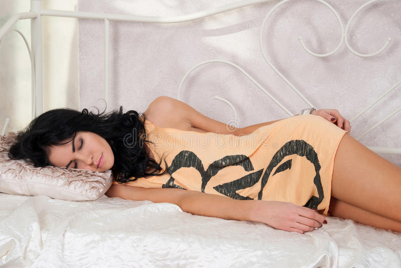 Bella ragazza castana che dorme sul letto fotografia stock libera da diritti