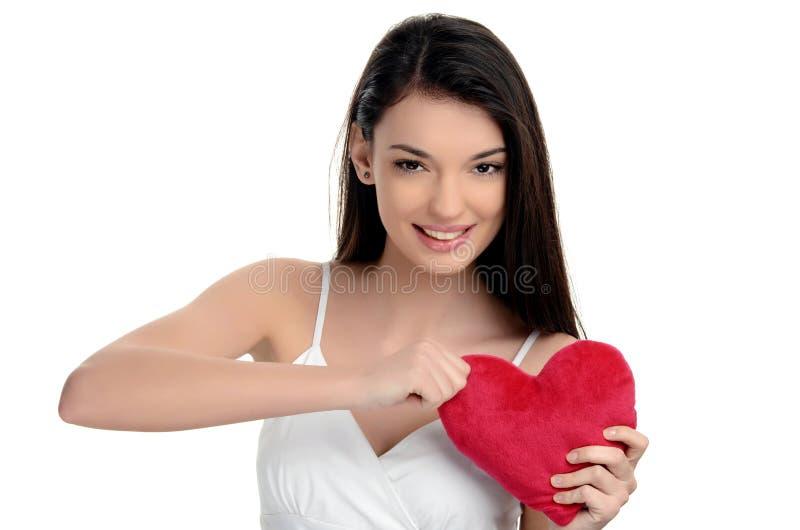 Bella ragazza castana che tiene un cuore rosso. Cuore rotto, senza amore, arrabbiato su amore. Donna che strappa su un cuore. Gior fotografie stock