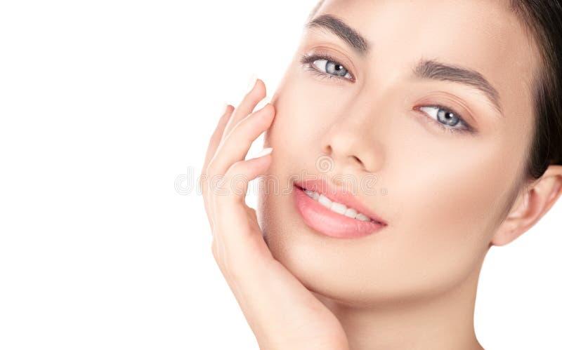 Bella ragazza castana che tocca il suo fronte Pelle fresca perfetta Ritratto di bellezza isolato su priorità bassa bianca Giovent fotografia stock