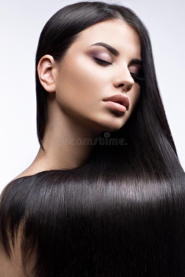 Bella ragazza castana nel movimento con i capelli perfettamente lisci e trucco classico Fronte di bellezza immagine stock libera da diritti