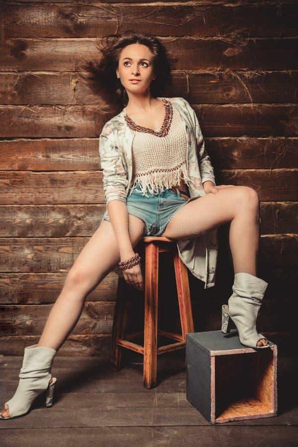 Bella ragazza castana in pantaloncini corti che posano nello studio su fondo di legno fotografia stock