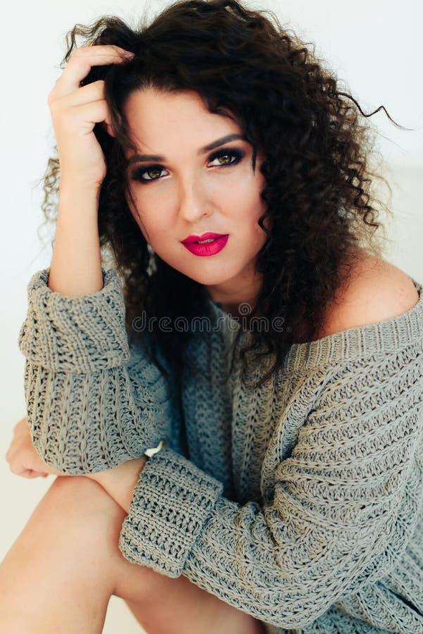 Bella ragazza castana riccia con i capelli di scarsità in un maglione caldo su un fondo bianco immagine stock libera da diritti