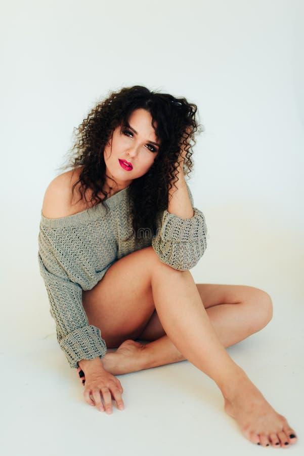 Bella ragazza castana riccia con i capelli di scarsità in un maglione caldo su un fondo bianco immagine stock
