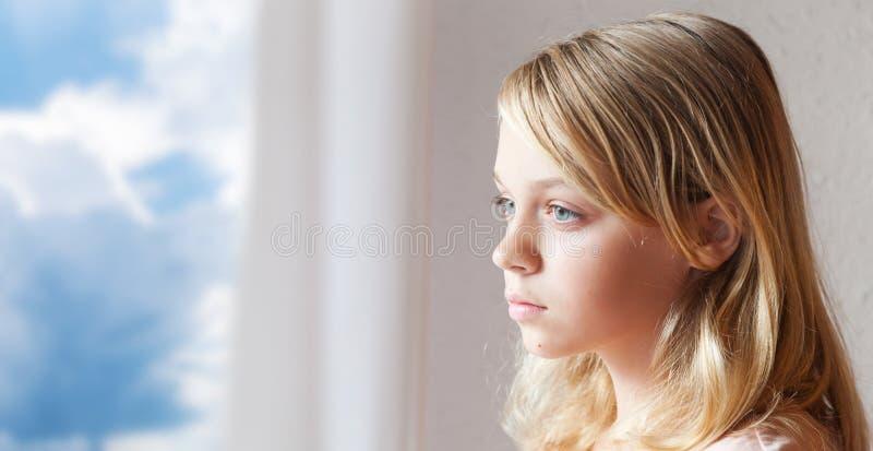 Bella ragazza caucasica bionda vicino alla finestra fotografie stock