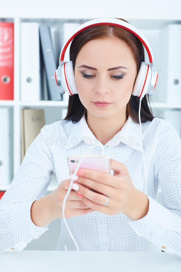 Bella ragazza che ascolta la musica in cuffie dallo smartphone in ufficio immagine stock libera da diritti