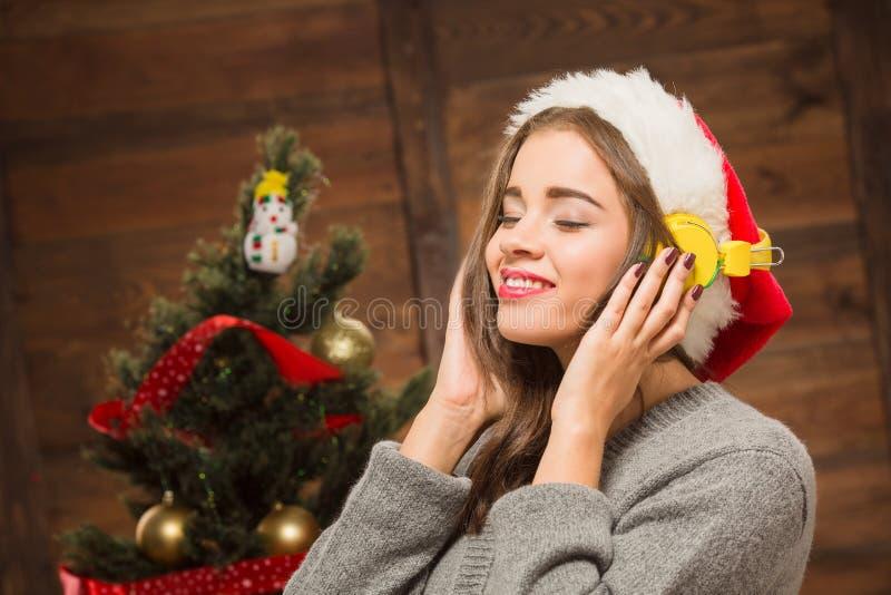 Bella ragazza che ascolta la musica davanti all'albero del nuovo anno fotografia stock