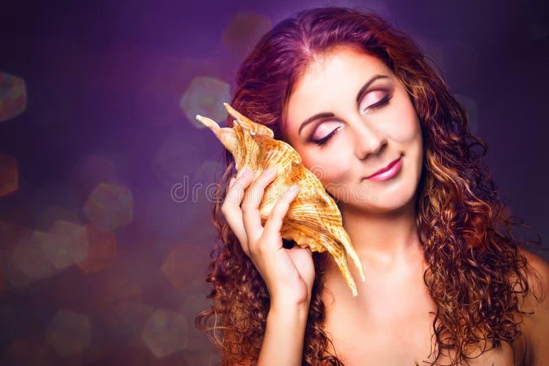 Bella ragazza che ascolta la musica del mare nella conchiglia del mare immagini stock libere da diritti