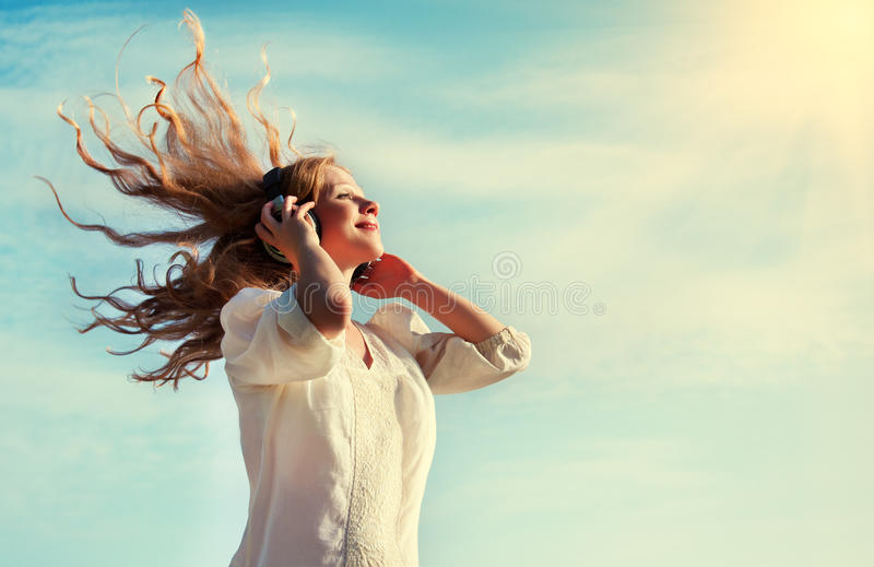 Bella ragazza che ascolta la musica sulle cuffie fotografie stock