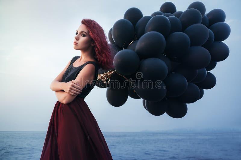 Bella ragazza che cammina con i palloni neri immagine stock libera da diritti