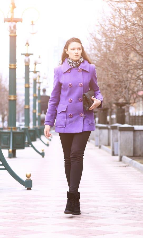 Bella ragazza che cammina giù la via in un cappotto porpora nella chiara ora immagini stock libere da diritti