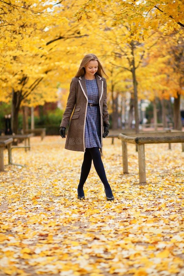 Bella ragazza che cammina nella sosta un giorno dell'autunno fotografia stock libera da diritti