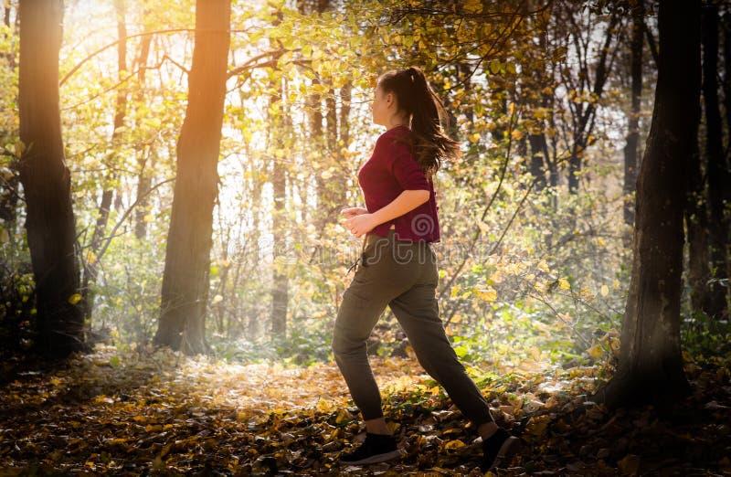 Bella ragazza che esegue la foresta della depressione in autunno fotografia stock