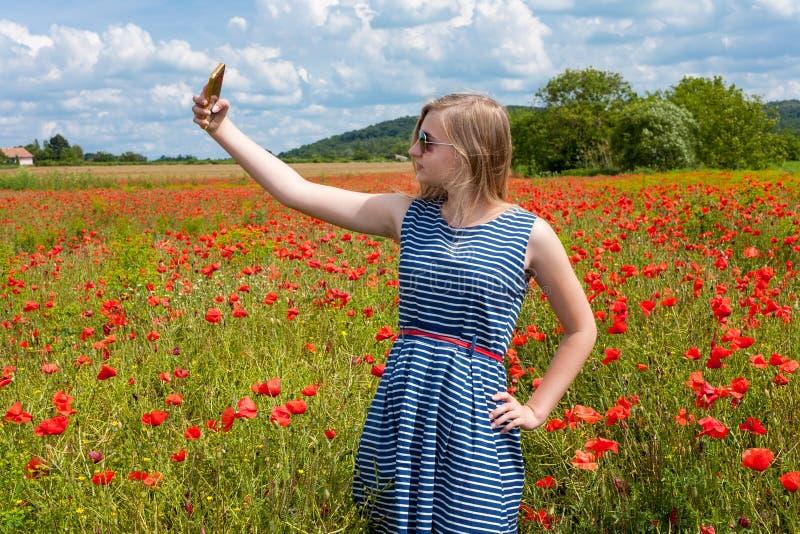 Bella ragazza che fa selfie con il telefono cellulare in un papavero immagine stock