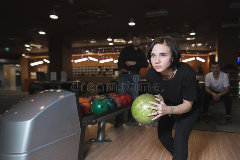 Bella ragazza che gioca bowling Donna con la palla per lanciare in mani nel moto fotografie stock libere da diritti