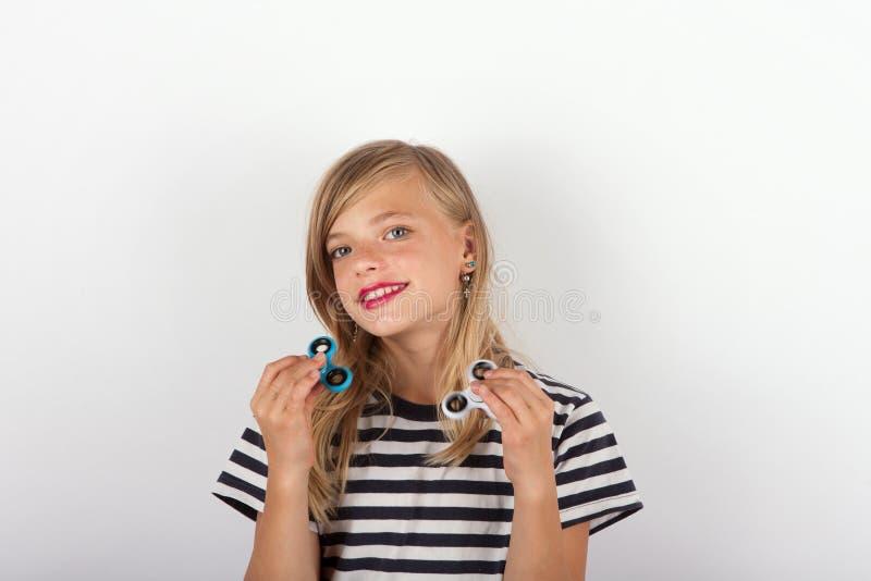 Bella ragazza che gioca con due filatori di irrequietezza fotografia stock libera da diritti