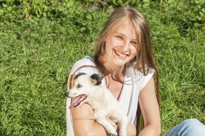 Bella ragazza che gioca con il cane fotografia stock libera da diritti